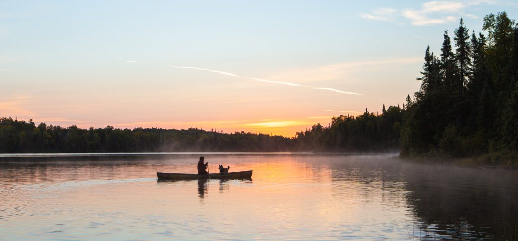 A man and a dog in a Northstar Canoe out Paddling. Photographer Bryan Bishop of BB Image, Thunder Bay
